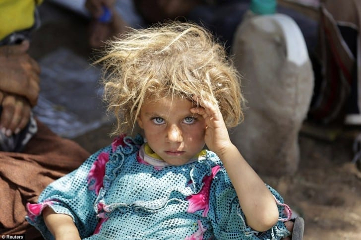 A girl from the minority Yazidi sect rests at the Iraqi-Syrian border crossing in Fishkhabour, Dohuk province after fleeing Isla